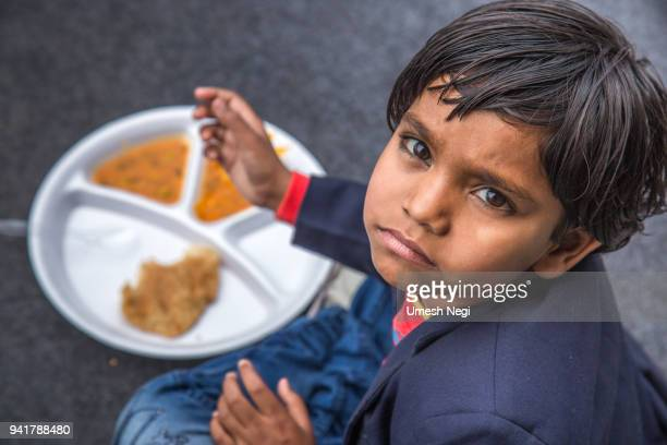 portrait of girl kid having mid-day meal in indian school. - poverty stock pictures, royalty-free photos & images