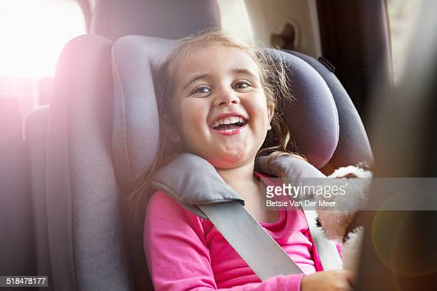 Portrait of girl laughing, sitting in car seat.