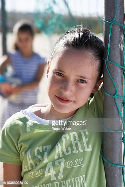 portrait of girl (12-13) leaning on goal post, other (8-9) in background - torpfosten stock-fotos und bilder