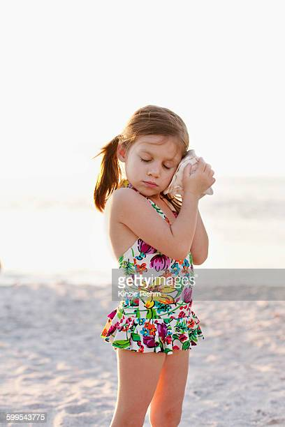 Portrait of girl listening to seashell at beach, Sanibel, Florida, USA