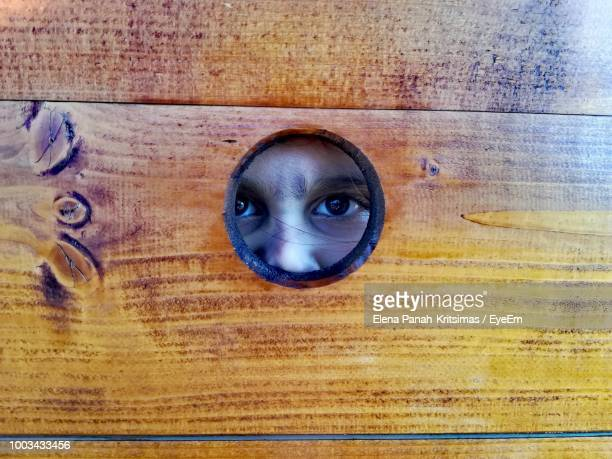 portrait of girl looking through hole in wood - peeping holes ストックフォトと画像