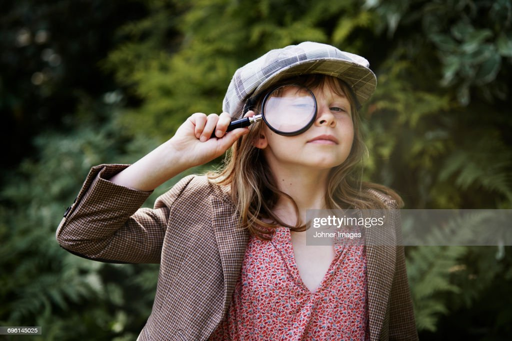 Portrait of girl looking through magnifying glass : Stock Photo