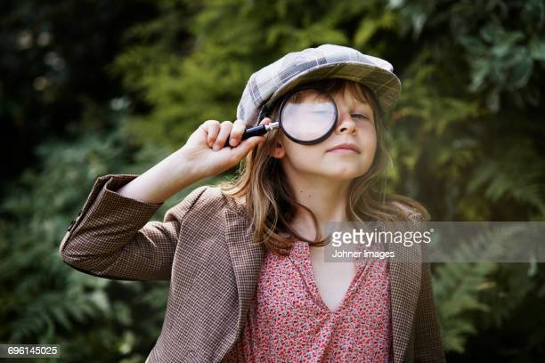 portrait of girl looking through magnifying glass - detective stock pictures, royalty-free photos & images