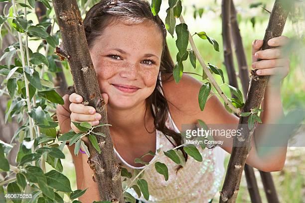 Portrait of girl looking through tree