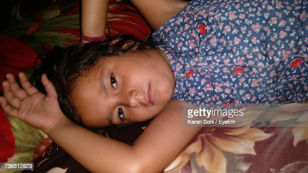 portrait of girl lying down on bed at home - karan soni stock photos and pictures