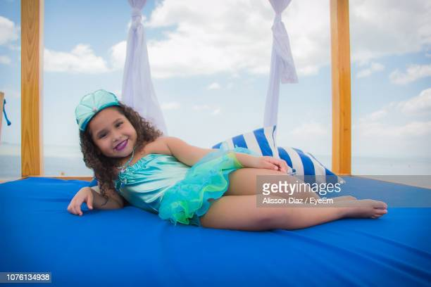 portrait of girl lying on bed against sky - alisson stock pictures, royalty-free photos & images