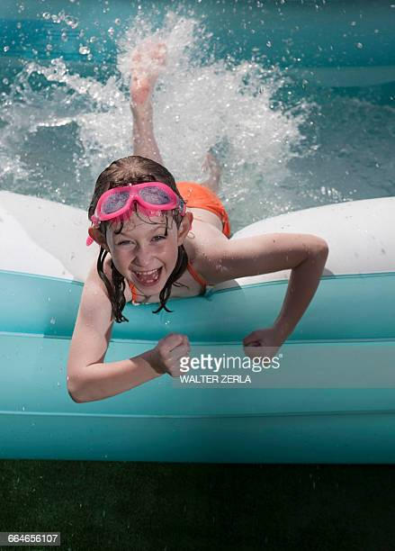 Portrait of girl lying on front splashing water in paddling pool
