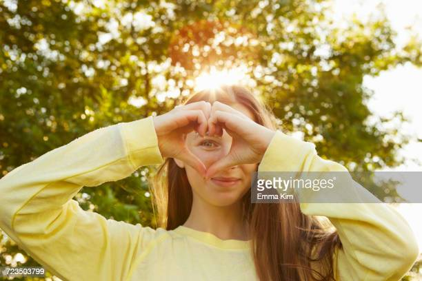Portrait of girl making heart shape with hands in park