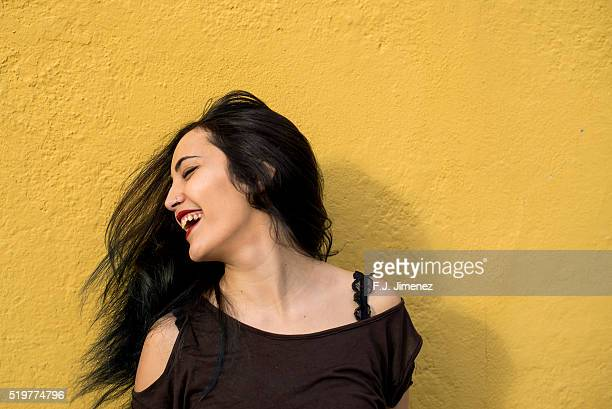Portrait of girl moving the head in front of yellow wall