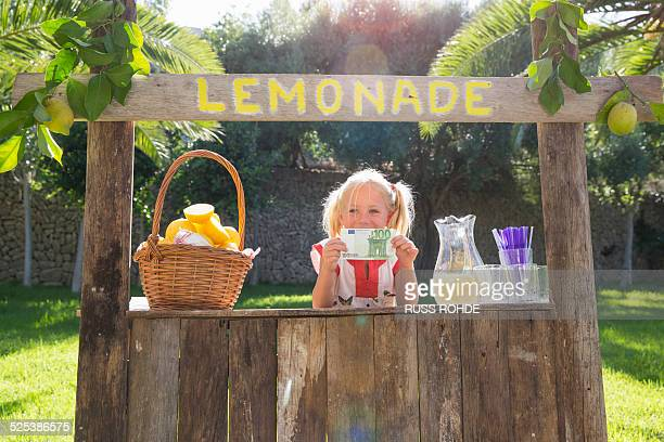 Portrait of girl on lemonade stand holding up one hundred euro note