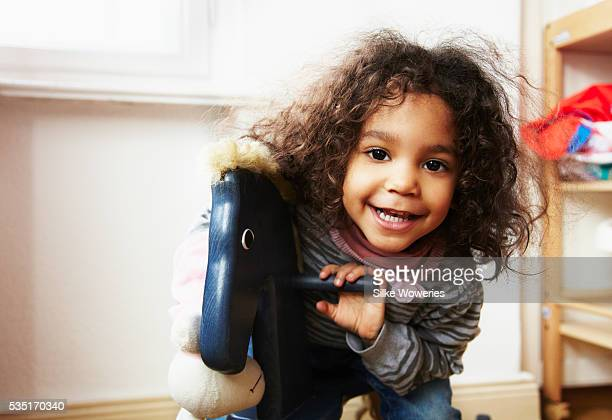 Portrait of girl (3-4) on rocking horse