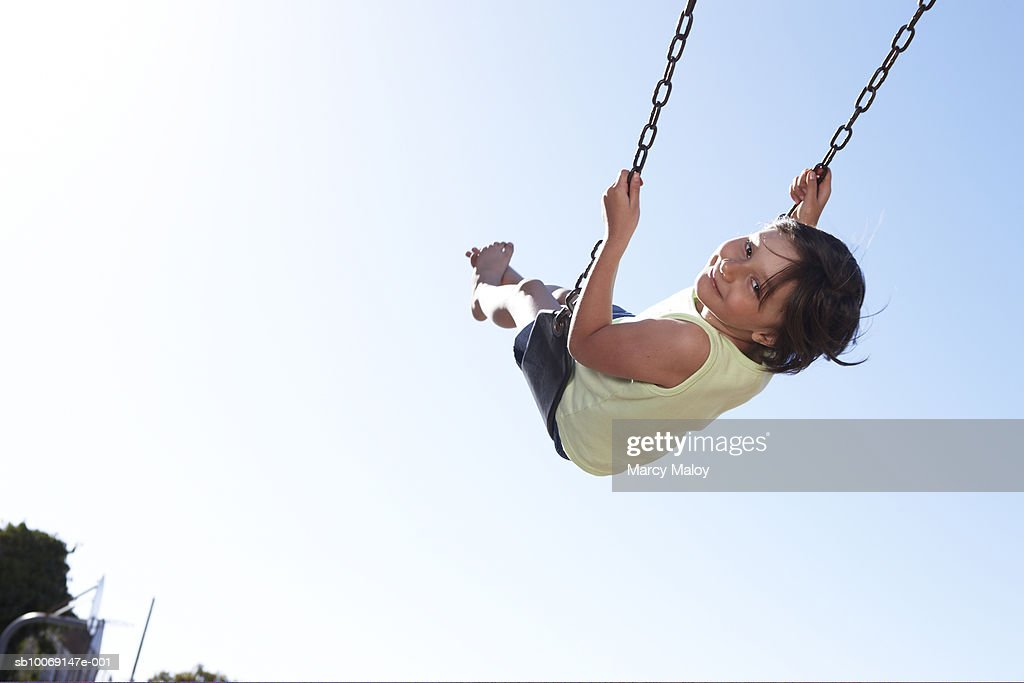 Portrait of girl (6-7) on swing, looking over shoulder : Stockfoto