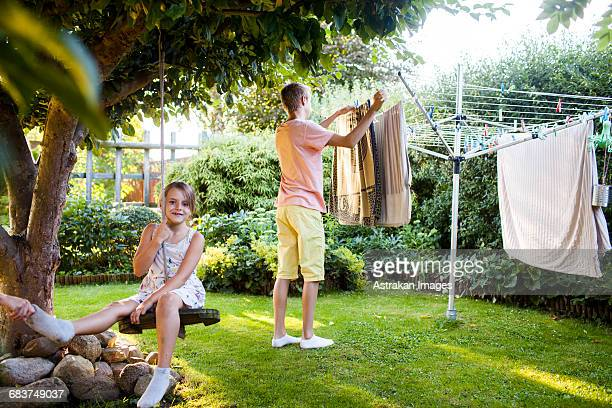 Portrait of girl on swing with brother doing laundry work in background at garden