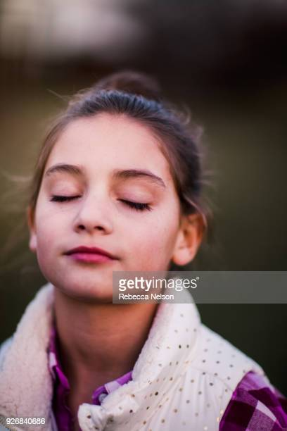 portrait of girl, outdoors, eyes closed, thoughtful expression - rebecca nelson stock pictures, royalty-free photos & images