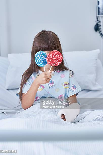 Portrait of girl patient holding lollipops in front of her eyes in hospital childrens ward