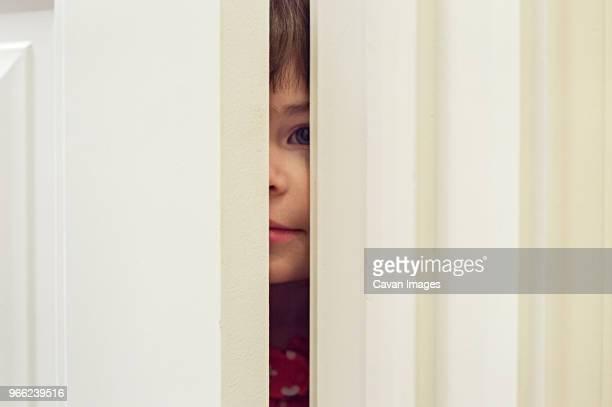 portrait of girl peeking through door - só uma menina - fotografias e filmes do acervo