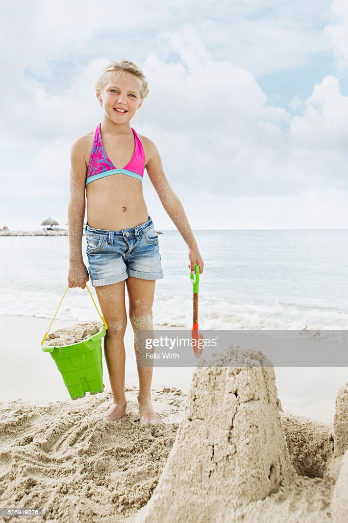 Portrait of girl (10-12) playing on beach in sand : Bildbanksbilder