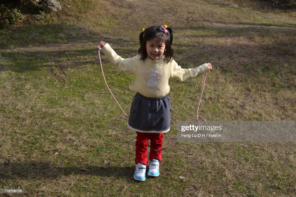 Portrait Of Girl Playing With Jumping Rope On Field : Photo