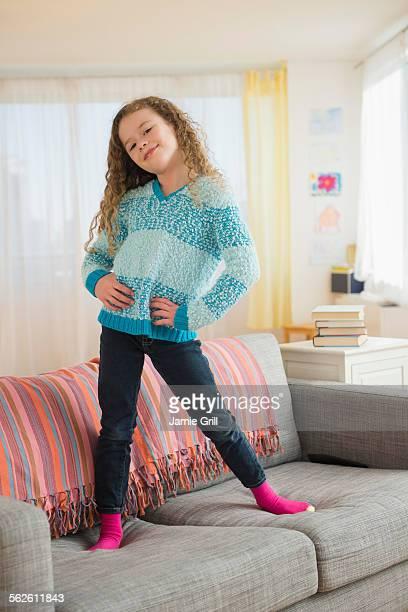 Portrait of girl (10-11) posing on sofa
