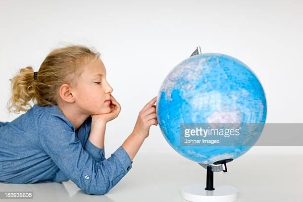 Portrait of girl reading globe