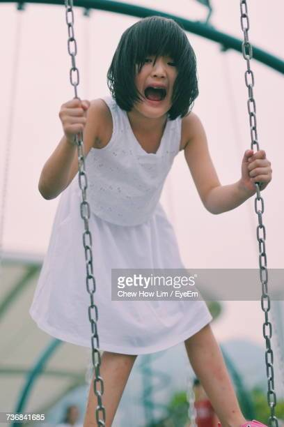 Portrait Of Girl Screaming While Standing On Swing At Playground During Sunset