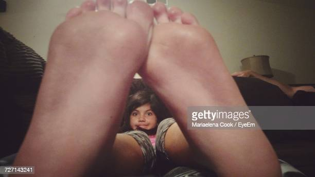 Portrait Of Girl Seen Through Feet At Home