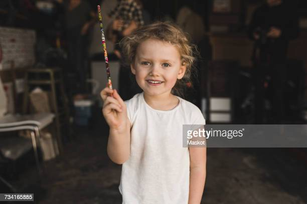 Portrait of girl showing magic wand in storage room