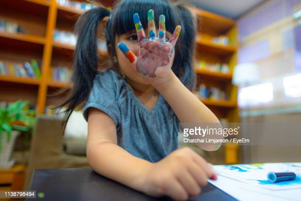portrait of girl showing painted hand at home - 4 girls finger painting stock photos and pictures