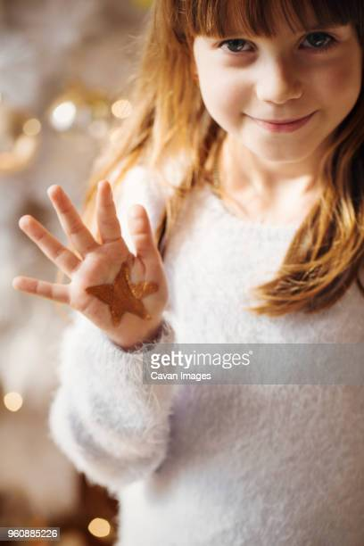 Portrait of girl showing star shape drawing on palm