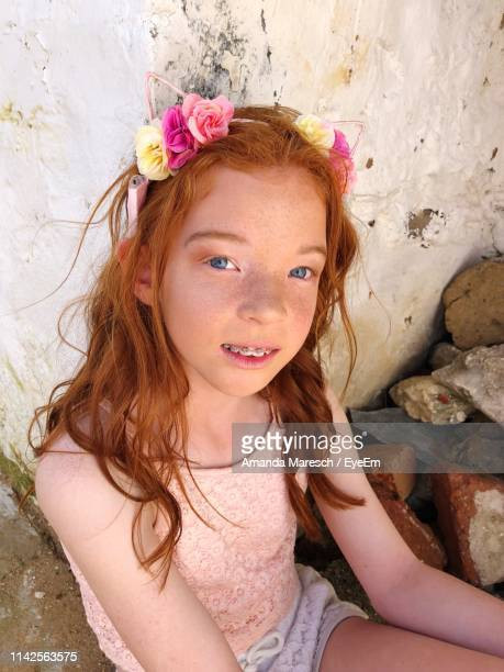 Portrait Of Girl Sitting Against Wall