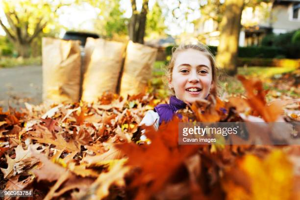 Portrait of girl sitting amidst autumn leaves