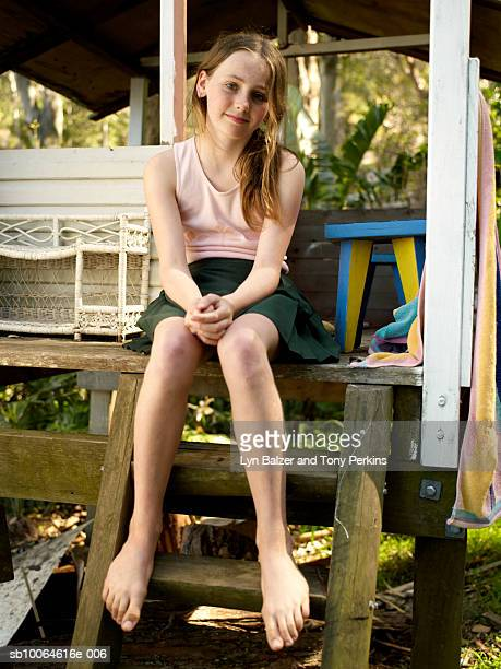 portrait of girl (10-11) sitting at entrance of cubby house - barefoot girl stock photos and pictures