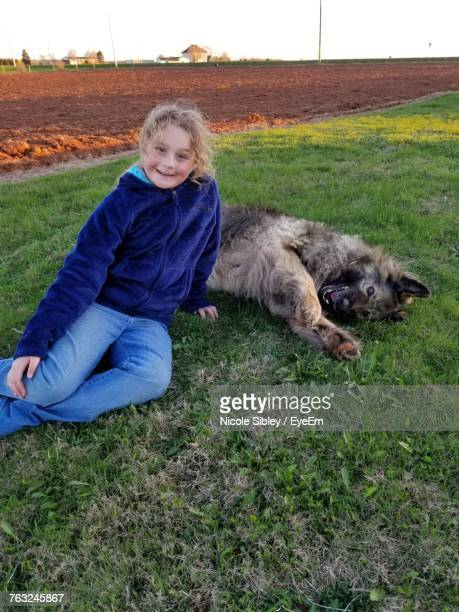 portrait of girl sitting by dog on field - sibley stock photos and pictures