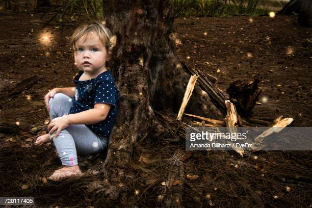 Portrait Of Girl Sitting By Tree Trunk On Field At Park
