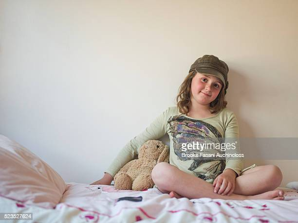 Portrait of girl (7-9) sitting on bed
