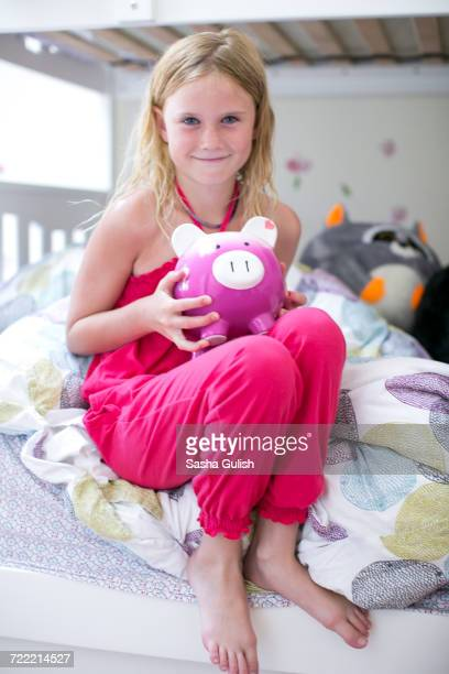 Portrait of girl sitting on bunk bed holding piggy bank