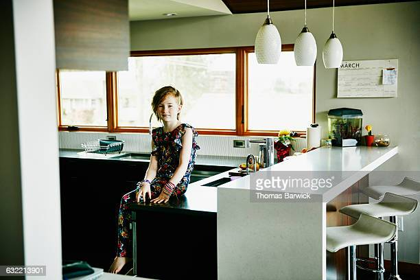 Portrait of girl sitting on countertop in kitchen