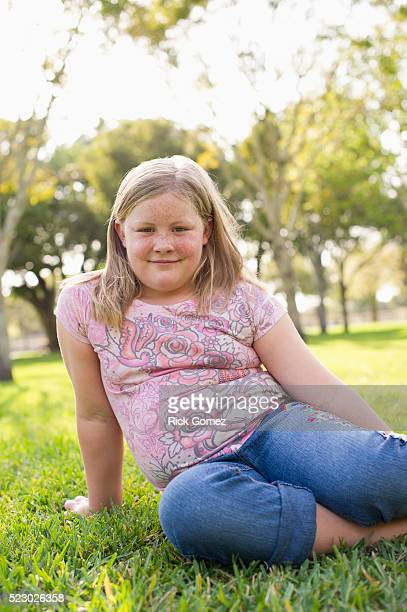 Portrait of girl (7-9) sitting on grass