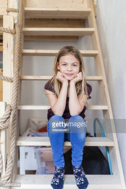 portrait of girl sitting on ladder of her loft bed - girls in socks stock photos and pictures