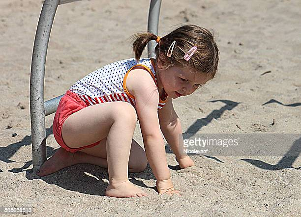 Portrait of girl (2-3) sitting on sand at playground