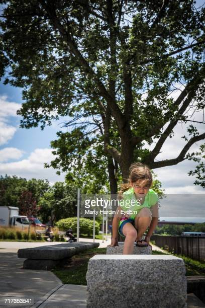portrait of girl sitting on seat at park - marty hardin stock photos and pictures
