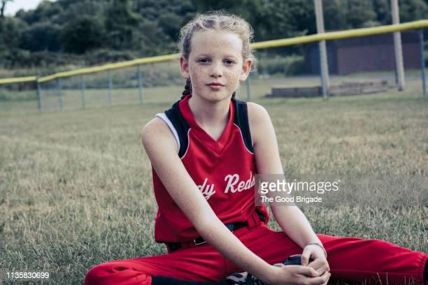 Portrait of girl sitting on softball field