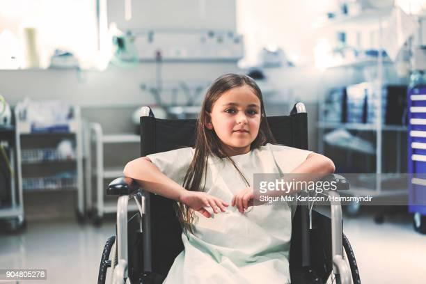 Portrait of girl sitting on wheelchair in hospital