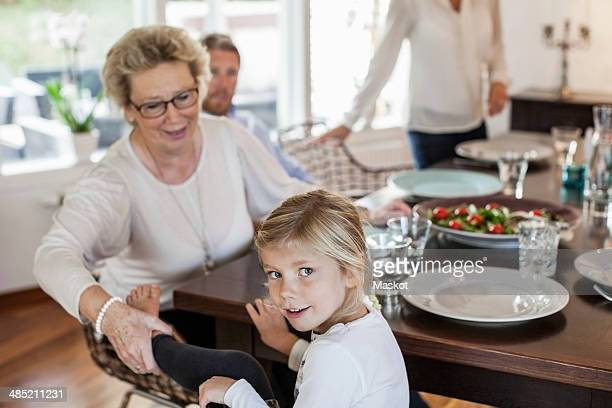 Portrait of girl sitting with family at dining table