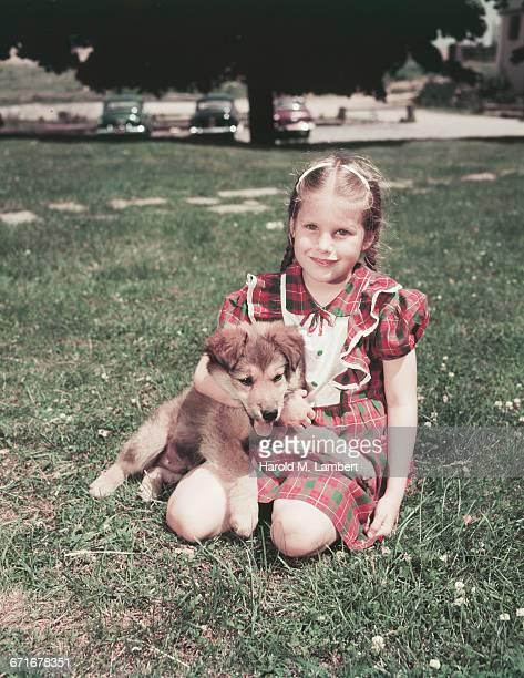 portrait of girl sitting with puppy  - mamífero con garras fotografías e imágenes de stock