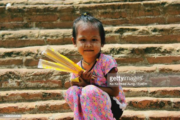 portrait of girl smiling sitting on steps - ko ko htike aung stock pictures, royalty-free photos & images