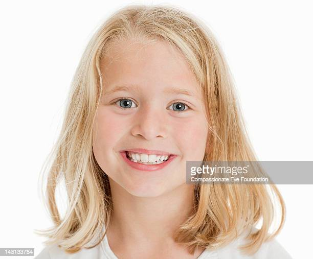 Portrait of girl (7-8), smiling, studio shot