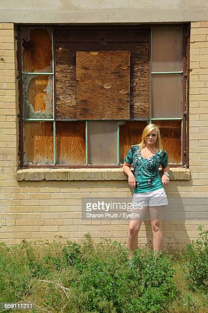 Portrait Of Girl Standing Against Old Abandoned Building In Grassy Field