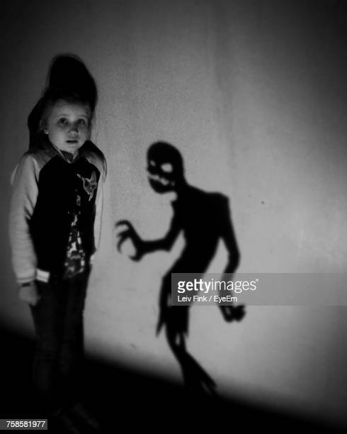 portrait of girl standing against wall during halloween - demons stock photos and pictures