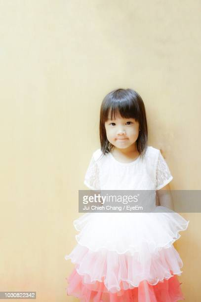 Portrait Of Girl Standing Against Wall